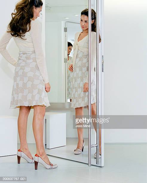Young woman looking in mirror of fitting room in clothing store