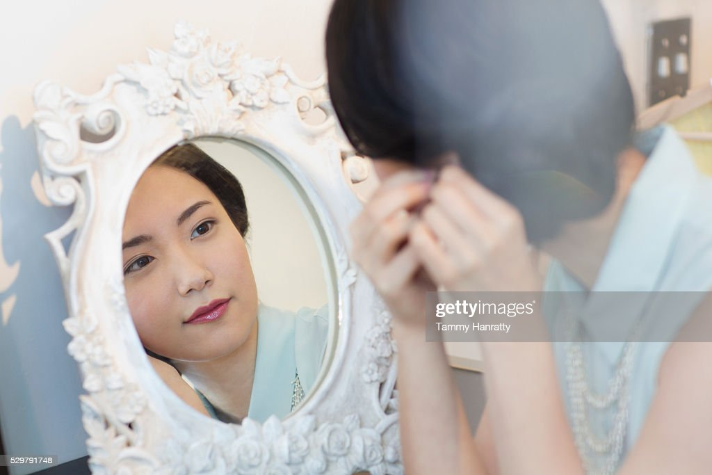 Young woman looking in mirror : Bildbanksbilder