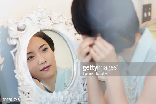 Young woman looking in mirror : Stockfoto