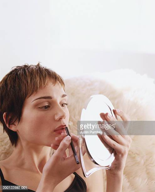 Young woman looking in mirror using lip pencil