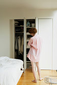 Young woman looking in open wardrobe, arms folded, rear view