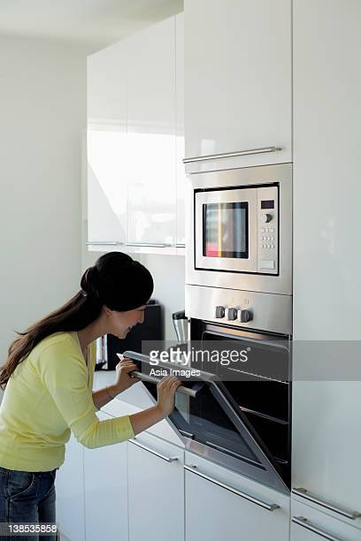 Young woman looking in oven