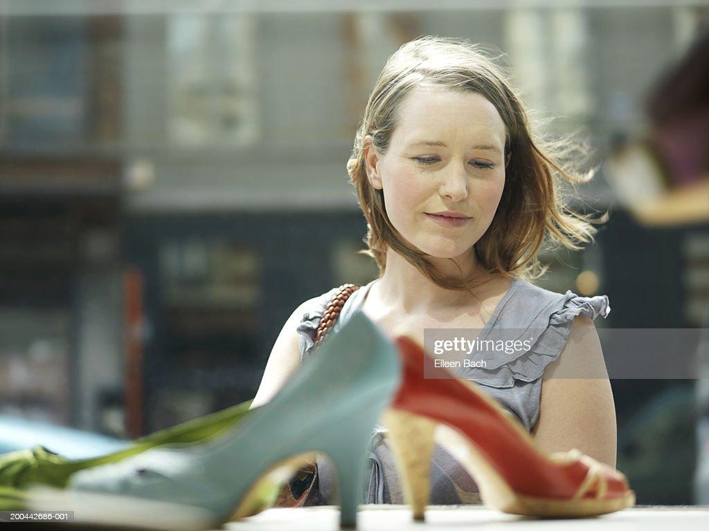 Young woman looking in shoe shop window, smiling, view through glass