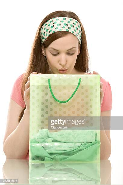 Young woman looking into shopping bag