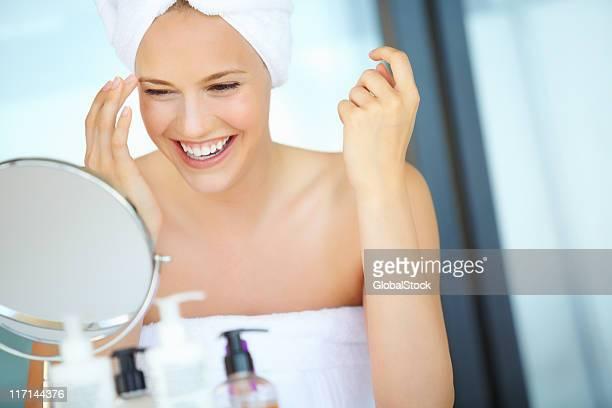 Jeune femme regardant dans le miroir et souriant