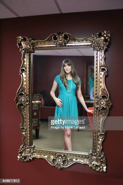 Young woman looking in vintage mirror frame on wall