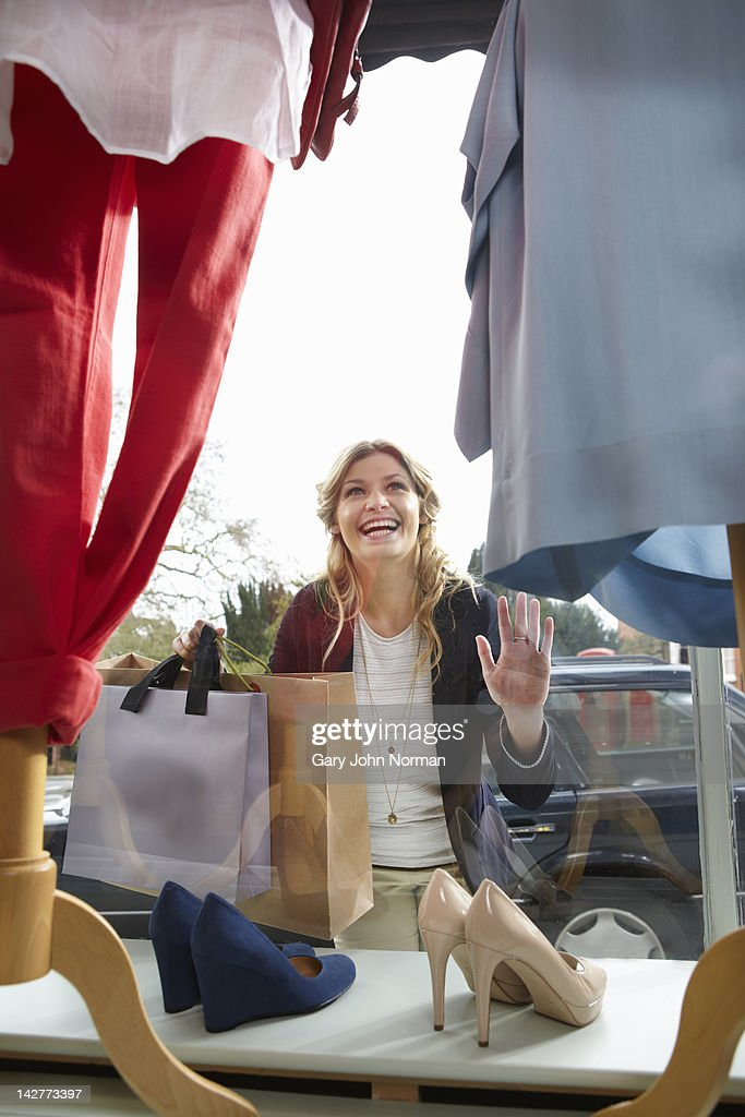 Young woman looking in window of boutique shop : Stock Photo