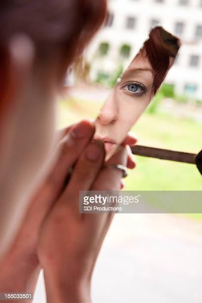 Junge Frau auf der Suche in einer zerbrochenen Spiegel