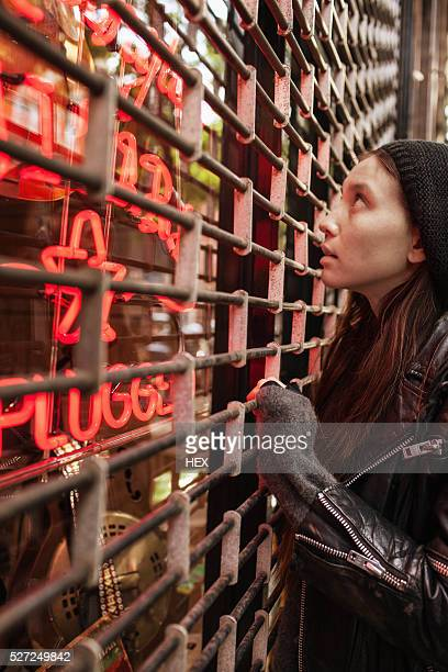 Young woman looking into a closed store