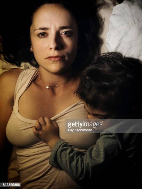 Young woman looking into camera as toddler sleeps