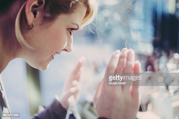 Young woman looking into shopping window.