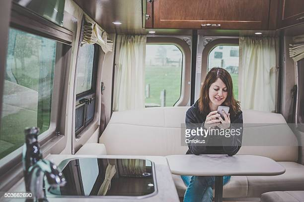 Young Woman Looking Mobile phone Inside Motorhome