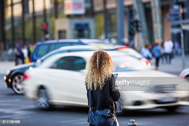 Young woman looking on her mobile phone, distracted from the city traffic