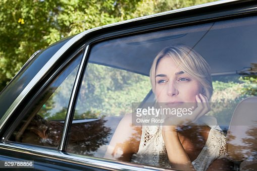 Young woman looking out a car window : Stock Photo