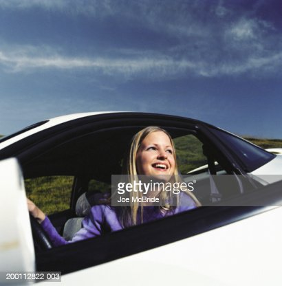 young woman looking out car window smiling stock photo