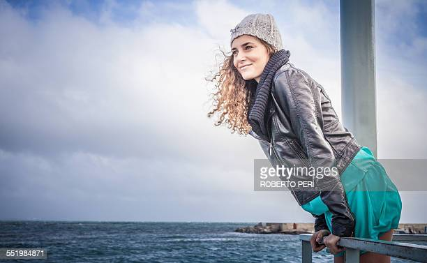 Young woman looking out from sea pier