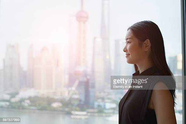 Young woman looking out of a window, China