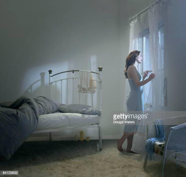 Young woman looking out of bedroom window.