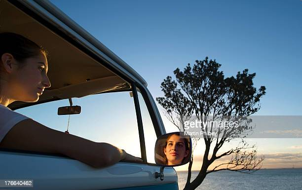 Young woman looking out of camper van window at dusk