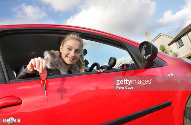 Young woman looking out of car window holding keys
