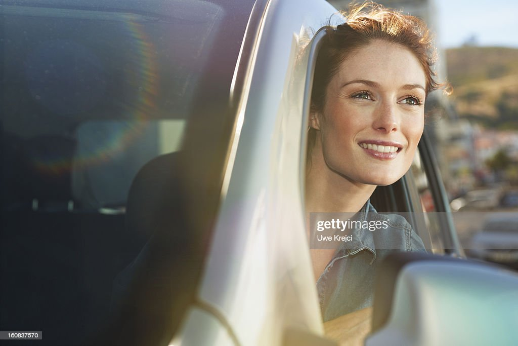 Young woman looking out of car window : Stock Photo
