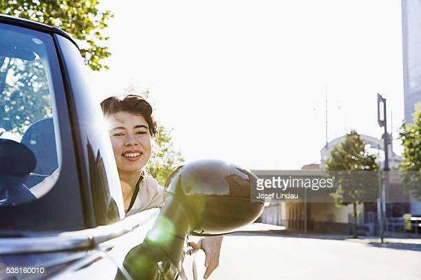 Young woman looking out of open top sports car
