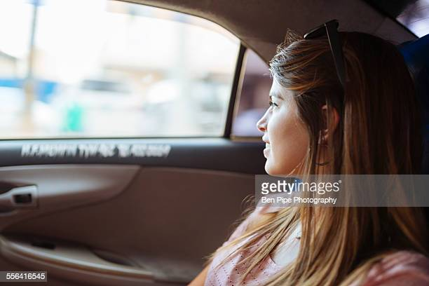 Young woman looking out of taxi window, Manila, Philippines