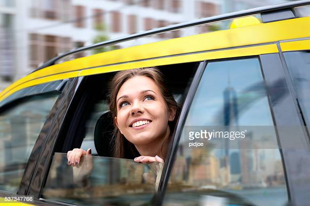 young woman looking out of taxi window to New York