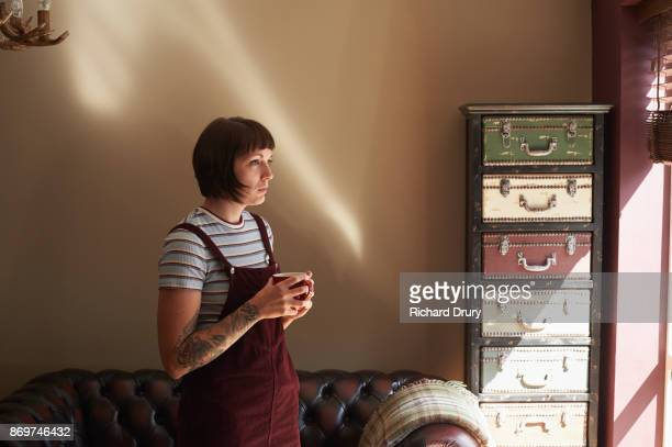 Young woman looking out of window holding coffee mug