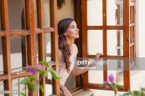 Young woman looking out of window : Stock Photo