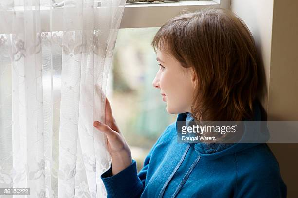 Young woman looking out of window.