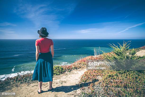 Young woman looking out over the ocean.