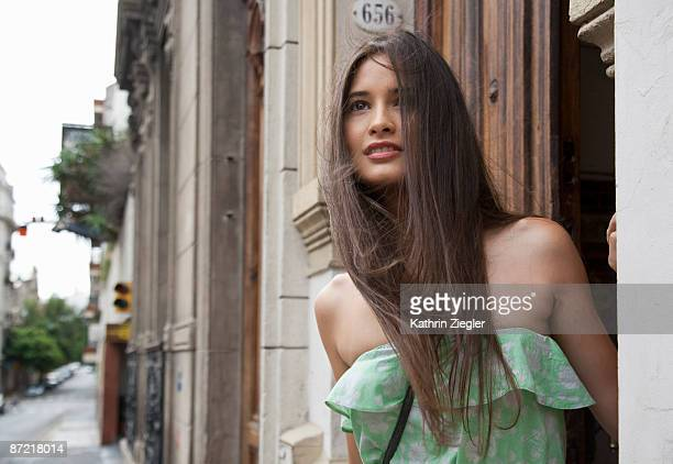 young woman looking out the door