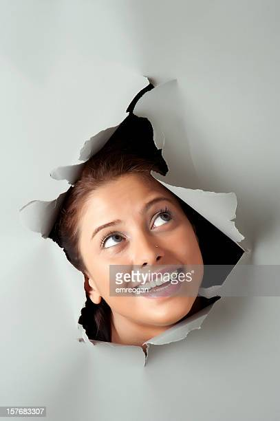 Young woman looking out through hole in grey paper