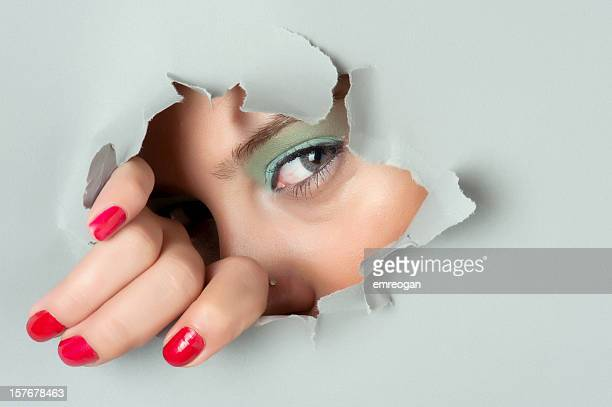 Young woman looking out through hole