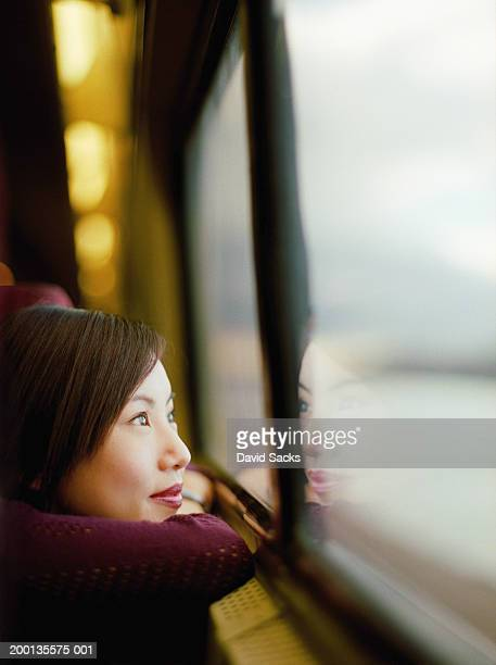 Young woman looking out train window, close-up, side view