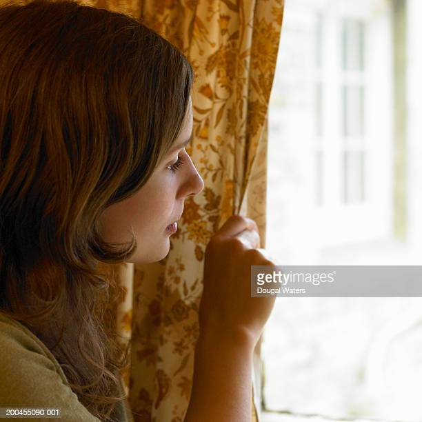 Young woman looking out window, holding back curtain, close-up