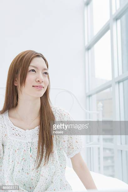 Young woman looking out window, smiling