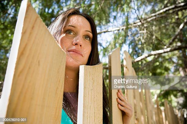 Young woman looking over fence, low angle view