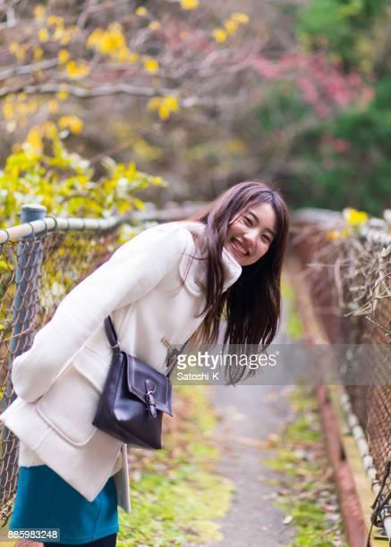 狭い橋の上の肩越しに見ている若い女性