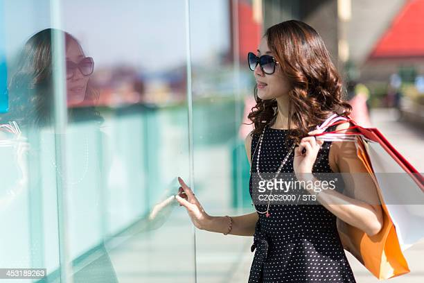 young woman looking through a shop window