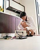 Young woman looking through handbag in kitchen