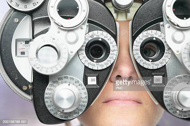 Young woman looking through phoropter during eye exam, close-up