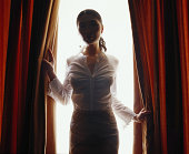Young woman looking through red curtains, back lit