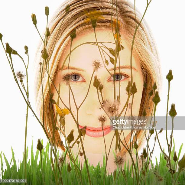Young woman looking through weeds and tall grass (Digital Composite)