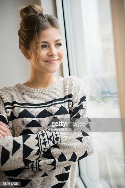 Young woman looking through window and smiling