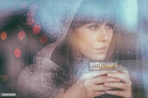 Young woman looking through window on rainy day
