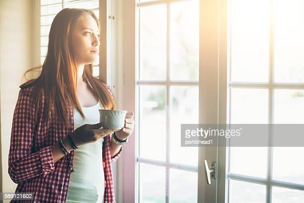 Jeune femme regardant à travers une fenêtre
