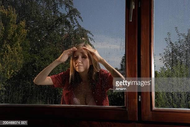 Young woman looking through window, standing outside in rain