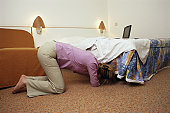 Young woman looking under bed, side view